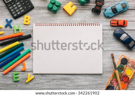 Top view of blank notebook, school supplies and toys on a white wooden desk.