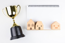 Top view of Blank notebook white paper, paper house model and Golden trophy isolated on white background with space for your message.Concept winner