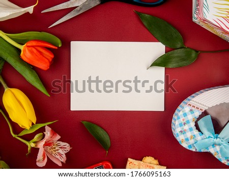 Top view of blank paper greeting card and tulip with alstroemeria flowers with a heart shaped gift box on red background