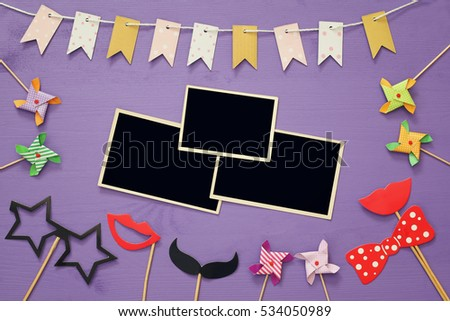 Top view of blank photo frames next to funny party accessories on purple wooden background