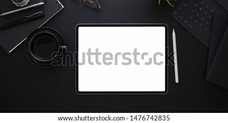 Top view of blank screen tablet on black desk background in dark stylish workplace and cup of coffee