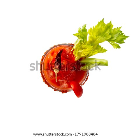 Photo of  Top view of Bloody Mary cocktail with vodka, lemon and tomato juice, tabasco sauce and ice cubes decorated with celery leaves and red pepper glass rim