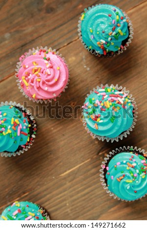 Top view of blue and pink icing cupcakes