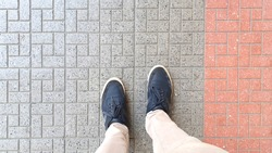 top view of blue casual shoes with beige pants standing on a street tile.