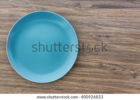 Top view of blue empty plate on wooden background with copy space