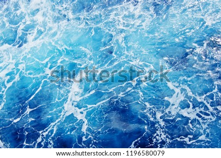 Top view of blue frothy sea surface, shot in the open sea