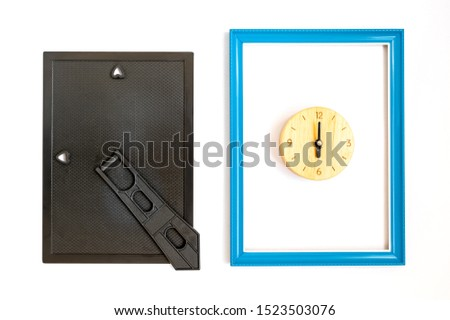 Top view of blue picture frame made wooden with clock inside. And the back cover black with stand. Placed on white background.