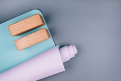 Top view of blue pink yoga mat and two wooden blocks on pastel grey background. Yoga pilates  Sport concept. Flat Lay. Copy space.