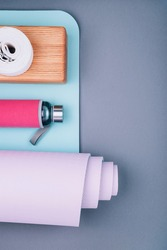Top view of blue pink yoga mat,glass water bottle, wooden block and twisted white belt on grey background.Yoga pilates  practice, relaxation and meditation accessories. Losing weight and sport concept