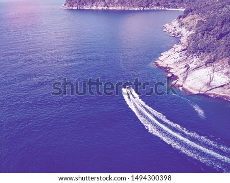 Top view of boat, leaving a white trail in blue deep water be the rocky coastline; background. Vessels. #1494300398