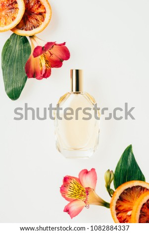 top view of bottle of aromatic perfume with flowers and grapefruit slices on white