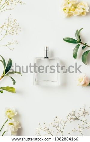 top view of bottle of perfume surrounded with flowers and green branches on white
