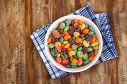 Top view of bowl with fruit cereal naturally and artificially fruit flavored sweetened corn puffs. Cereal fruity shapes