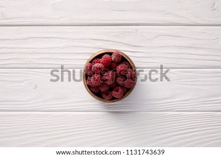 top view of bowl with ripe raspberries on white wooden table #1131743639