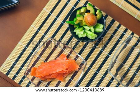 Top view of bowls with avocado, cucumber and salmon cut ready to prepare sushi