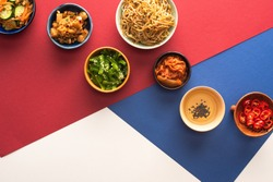 top view of bowls with korean traditional side dishes and oil on blue, crimson and white