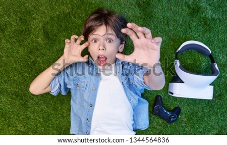 Top view of boy lying on grass with VR goggles and gamepad and looking with amazement at camera gesturing with hands