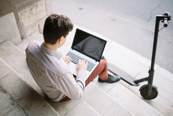 Top view of boy using laptop while sitting on stairs. High angle view of man using laptop with blank screen while sitting on stairs near electric scooter.