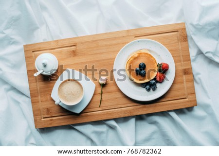 top view of breakfast in bed with tasty pancakes and coffee on wooden tray