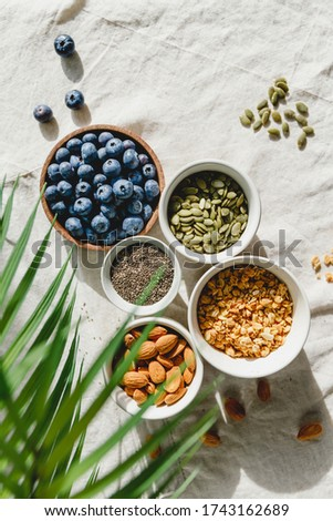 Top view of breakfast ingredients like cereal, almond, blueberry, pepitas and chia seeds on a linen cloth decorated with palm leaf. Foto d'archivio ©