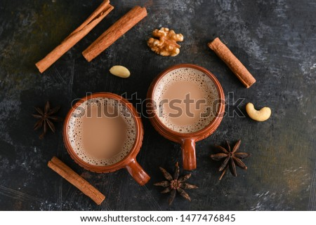 Top view of brewed hot herbal or spiced, aromatic milk tea with spices and dry fruits in Kerala India. Two cups of organic ayurvedic drink or Chai is good in winter for immunity boosting and health.