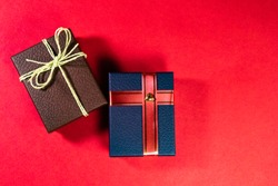 Top view of brown and blue gift box with attractive  ribbons on red background with copy space in wedding gifs concept