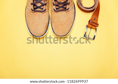 Top view of Brown boots and brown belt on yellow background. Copyspace, flat lay. Traveling boots, minimalist. Fashion accessories concept. #1182699937