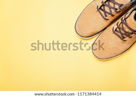 Top view of Brown boots on yellow background. Copyspace, flat lay. Traveling boots, minimalist. #1171384414