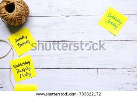 Top view of brown rope and yellow sticky notes written with 'MONDAY,TUESDAY,WEDNESDAY,THURSDAY,FRIDAY,SATURDAY,SUNDAY' on white wooden background. #783822172
