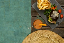 Top view of burger, french fries and freshly squeezed orange juice near swimmingpool
