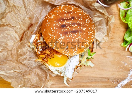 Top view of burger with egg, bacon, tomato ketchup on a wooden board