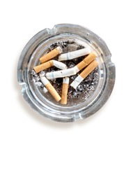 top view of burned cigarette in ashtray on white background