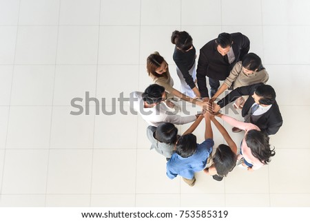 top view of business multi-ethnic partners teamwork, team join hand together at office, synergy concept, copy space