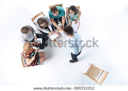 Top view of business people in a meeting on white background. all sitting with notepad and pen. speaker standing and saying something