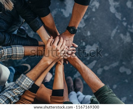 Top view of business people putting their hand together. Business team stacking hands over each other.