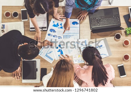 Top view of businessman executive in group meeting with other businessmen and businesswomen in modern office with laptop computer, coffee and document on table. People corporate business team concept. #1296741802