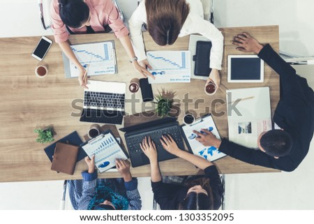 Top view of businessman executive in group meeting with other businessmen and businesswomen in modern office with laptop computer, coffee and document on table. People corporate business team concept. #1303352095