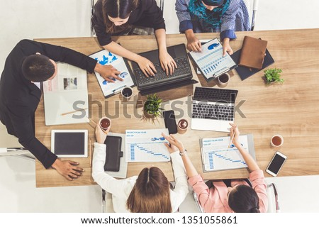 Top view of businessman executive in group meeting with other businessmen and businesswomen in modern office with laptop computer, coffee and document on table. People corporate business team concept. #1351055861