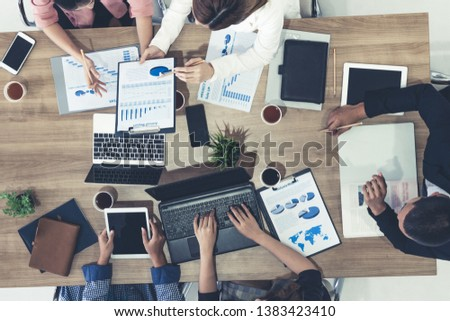 Top view of businessman executive in group meeting with other businessmen and businesswomen in modern office with laptop computer, coffee and document on table. People corporate business team concept. #1383423410