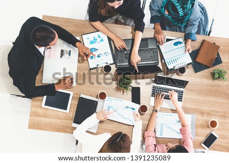 Top view of businessman executive in group meeting with other businessmen and businesswomen in modern office with laptop computer, coffee and document on table. People corporate business team concept. #1391235089