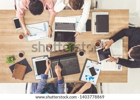 Top view of businessman executive in group meeting with other businessmen and businesswomen in modern office with laptop computer, coffee and document on table. People corporate business team concept. #1403778869