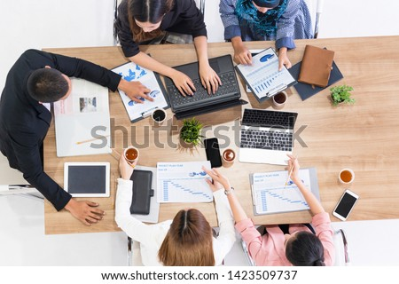 Top view of businessman executive in group meeting with other businessmen and businesswomen in modern office with laptop computer, coffee and document on table. People corporate business team concept. #1423509737