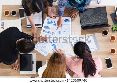 Top view of businessman executive in group meeting with other businessmen and businesswomen in modern office with laptop computer, coffee and document on table. People corporate business team concept. #1423509740