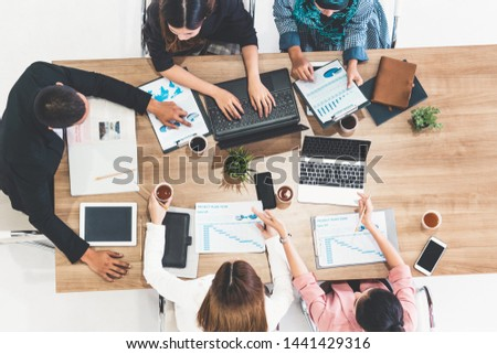 Top view of businessman executive in group meeting with other businessmen and businesswomen in modern office with laptop computer, coffee and document on table. People corporate business team concept. #1441429316