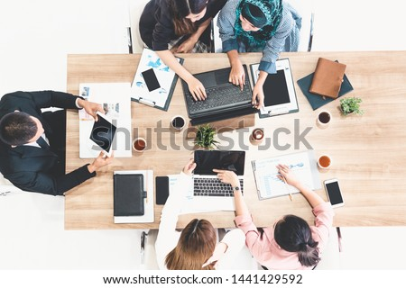 Top view of businessman executive in group meeting with other businessmen and businesswomen in modern office with laptop computer, coffee and document on table. People corporate business team concept. #1441429592