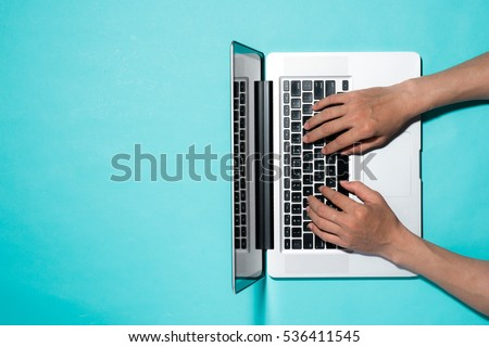 Top view of businessman hands busy using laptop at office desk, with copyspace