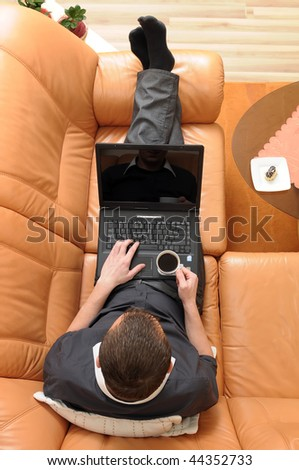 Top view of businessman holding a cup of coffee and working on portable computer on luxurious sofa.