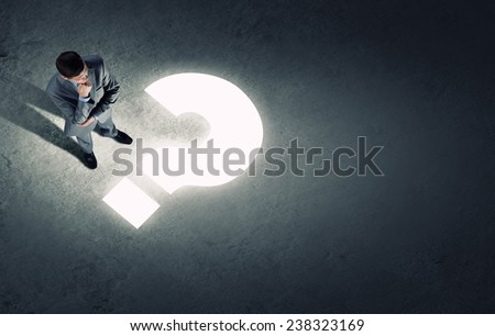 Top view of businessman looking at question mark on floor