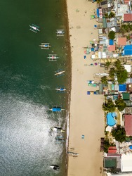 Top view of Calayo Beach, Nasugbu, Batangas. A fishing village and tourist spot. Many small outrigger boats anchored near the shore.