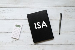 Top view of calculator,pen and notebook written with ISA (individual saving account) on white wooden background.